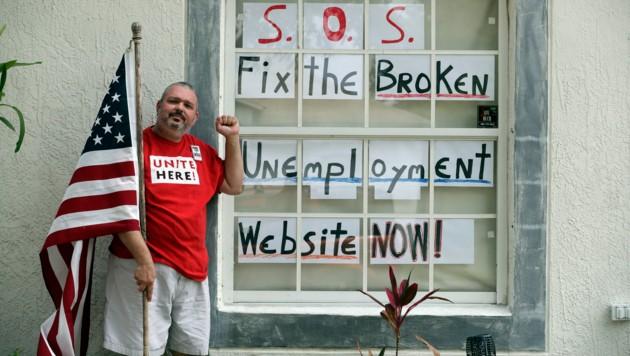 Ein aufgrund der Corona-Pandemie arbeitslos gewordener ehemaliger Mitarbeiter von Disney World in Florida macht vor seinem Heim darauf aufmerksam, dass die Website zur Arbeitslosmeldung in dem südlichen Bundesstaat derzeit nicht funktioniert. (Bild: AP)