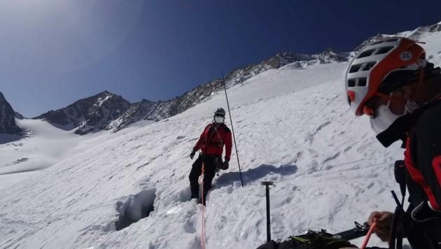 Bergretter mit Schutzmaske an der Stelle, wo der Alpinist in die Gletscherspalte stürzte (Bild: ZOOM.TIROL)