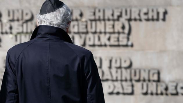 Mit einer Kippa steht ein Teilnehmer vor der Inschriftenwand vor Beginn der Gedenkveranstaltung zum 75. Jahrestag der Befreiung des KZ Bergen-Belsen. (Bild: APA/dpa/Peter Steffen)