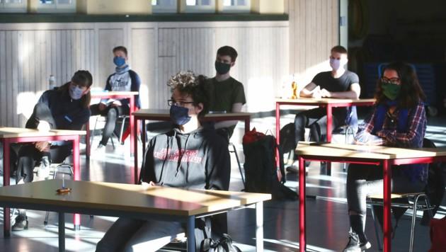 Schüler mit Mundschutz sitzen bei der Prüfungsvorbereitung für das deutsche Abitur in einer zum Schulraum umfunktionierten Turnhalle. In Österreich startet die Schule für Maturanten am Montag wieder. (Bild: APA/dpa-Zentralbild/Bodo Schackow)