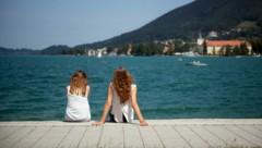 Zwei Frauen sitzen bei Sonnenschein in Rottach-Egern in Bayern am Tegernsee. (Bild: APA/dpa/Daniel Naupold)