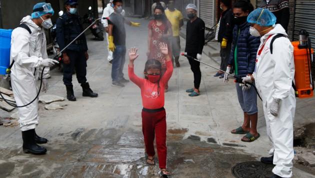 Nepal: Ein hungerndes Mädchen muss durch die Desinfektion, um Gratis-Essen zu bekommen. (Bild: ASSOCIATED PRESS)