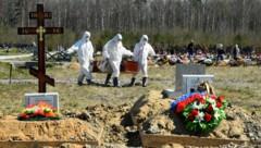 Friedhofsmitarbeiter bringen einen Covid-Verstorbenen zum Grab. (Bild: AFP)