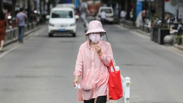 Eine Frau mit Faceshield und Maske in der Metropole Wuhan (Bild: AFP)