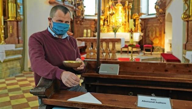 Pfarrer Wolfgang Toberer zeigt es vor: Die Hostien werden auf Servietten gelegt. (Bild: Sepp Pail)