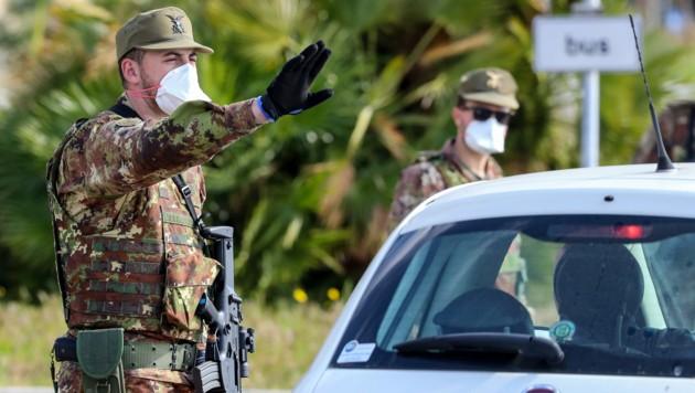 Italienische Soldaten kontrollieren Fahrzeuge bei der Einreise nach Italien. (Bild: AFP)