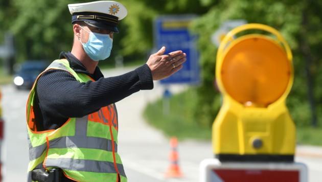 Ein deutscher Grenzpolizist winkt Einreisenden aus Österreich am Grenzübergang Kiefersfelden weiter. Es gibt nur mehr stichprobenartige Kontrollen. (Bild: APA/AFP/Christof STACHE)