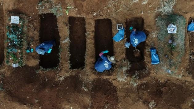 Arbeiter heben in einem Vorort von Sao Paulo in Brasilien Gräber für Opfer der Coronavirus-Pandemie aus. (Bild: AFP)