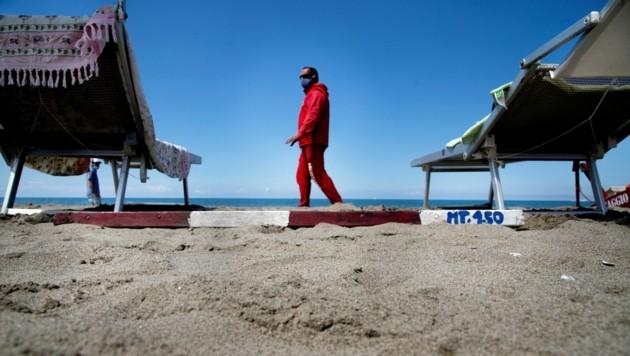 Ein Rettungsschwimmer überprüft den Abstand der Liegen am Strand. (Bild: AFP)
