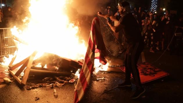In der Nähe des Weißen Hauses in der Hauptstadt Washington zünden Demonstranten eine US-Flagge an. (Bild: AP)