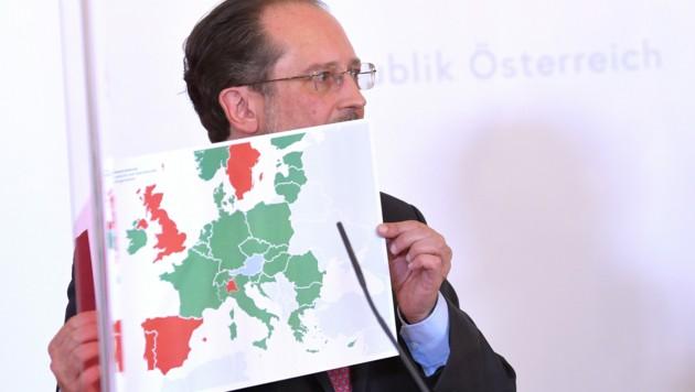 """Außenminister Schallenberg mit einer Karte der """"neuen Reisefreiheit"""" (Bild: APA/ROLAND SCHLAGER)"""