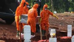Arbeiter in Schutzanzügen tragen den Sarg eines Covid-19-Toten. (Bild: AP)
