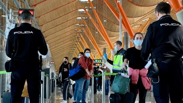 Polizisten überprüfen Passagiere, die von Paris nach Madrid geflogen waren. (Bild: AFP)