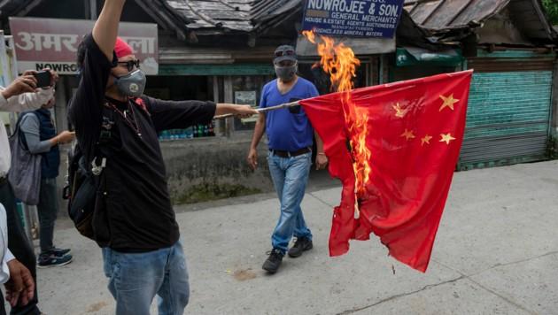Ein tibetanischer Aktivist verbrennt eine chinesische Flagge als Zeichen des Protests gegen die chinesische Besatzung indischen Territoriums und Tibets. (Bild: AP)