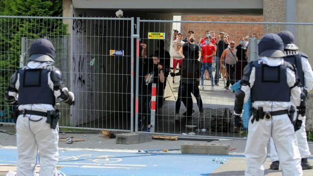 Weil die Polizei einschritt, als mehrere Bewohner das abgeriegelte Areal verlassen wollten, flogen wenige später Pflastersteine und andere Gegenstände auf die Sicherheitskräfte (Bild: AP)