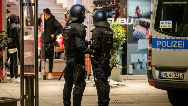 Einheiten der Polizei stehen vor einem zerstörten Geschäft in der Stuttgarter Königstraße. (Bild: APA/dpa/Christoph Schmidt)