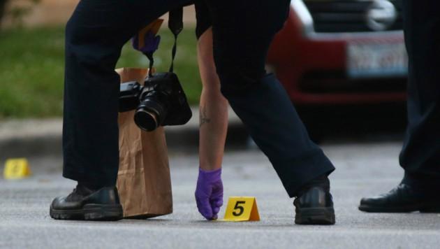 Ein Ermittler der Chicagoer Polizei beim Aufheben einer Patronenhülse. (Bild: John J. Kim/Chicago Tribune via AP)