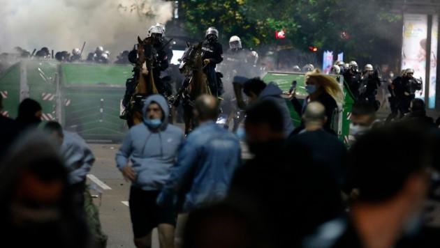 Serbische Polizisten versuchten die Versammlungen vor dem Parlamentsgebäude in Belgrad aufzulösen. (Bild: AP Photo/Darko Vojinovic)