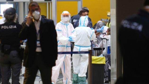 Mitarbeiter des italienischen Gesundheitsministeriums untersuchen Passagiere, die am Dienstag per Flugzeug aus Bangladesch in Rom gelandet sind. (Bild: AP)