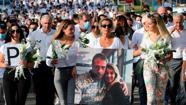 Die Frau des Busfahrers trägt ein Foto von sich und ihrem Liebsten und führt dabei den Trauermarsch an. (Bild: Associated Press)