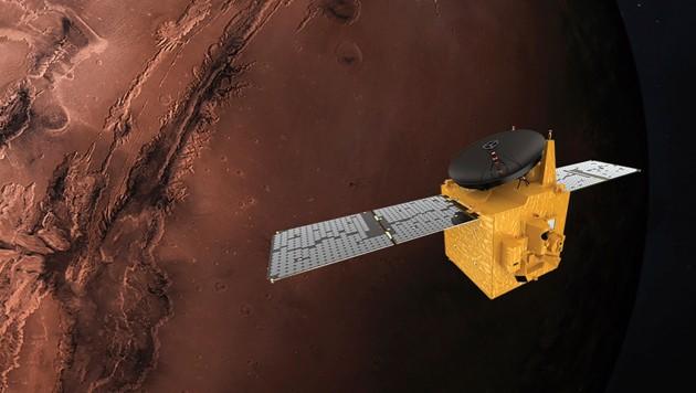 """Die künstlerische Illustration zeigt die Sonde """"Hope"""" vor dem Roten Planeten. (Bild: AP)"""