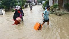 Menschen bringen sich und ihre Habseligkeiten in Sicherheit. (Bild: AP Photo/Khaizuran Muchtamir)