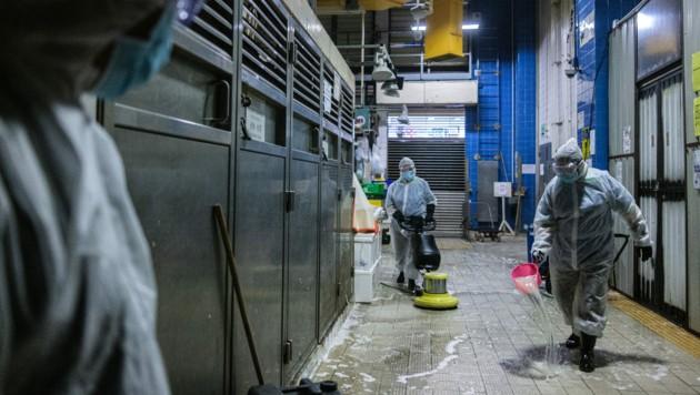 Die Hygienemaßnahmen in Hongkong wurden wieder verschärft - unter anderem werden die Märkte großflächig desinfiziert. (Bild: ANTHONY WALLACE / AFP)