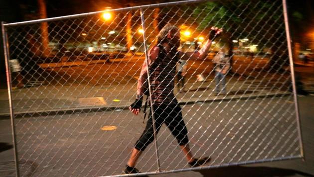 """Ein Demonstrant trägt eine Absperrung weg - noch effektiver war der Protest der """"nackten Athena""""."""
