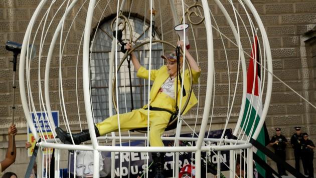 Die 79-Jährige sitzt im knallgelben Outfit im Vogelkäpfig, um einem Kanarienvogel ähnlich zu sehen. (Bild: APA/AP)