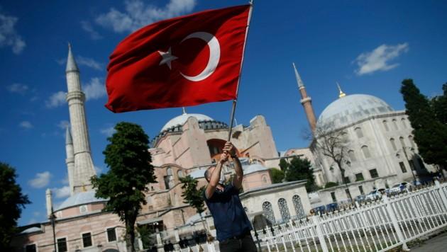 Von vielen Anhängern Erdogans wird der Schritt bejubelt. Am Bild sehen Sie einen Mann mit der türkischen Flagge vor der Hagia Sophia. (Bild: AP)