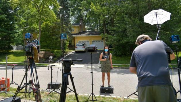 Journalisten und Kamerateams halten vor dem Tatort die Stellung.