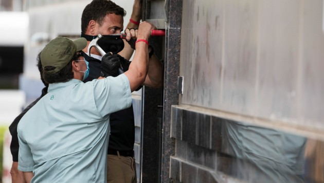 Bundesbeamte und ein Schlosser arbeiten an einer Tür, um das frei gewordene Gebäude des Generalkonsulats von China zu betreten. (Bild: AP)