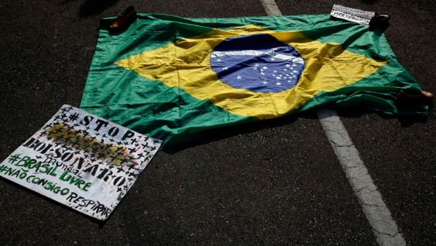"""Eine brasilianische Flagge mit eine Transparent mit den portugiesischen Worten """"Stoppt Bolsonaro, Freiheit für Brasilien, Ich kann nicht atmen"""" liegt am Boden."""