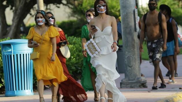 Menschen mit Schutzmasken am Ocean Drive in Miami Beach, Florida (Bild: AP)