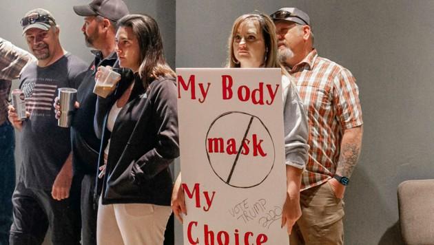 Eine US-Bürgerin protestiert mit einem Transparent für ihr Recht, keine Schutzmaske zu tragen - und wirbt für Trumps Wiederwahl. (Bild: AP)