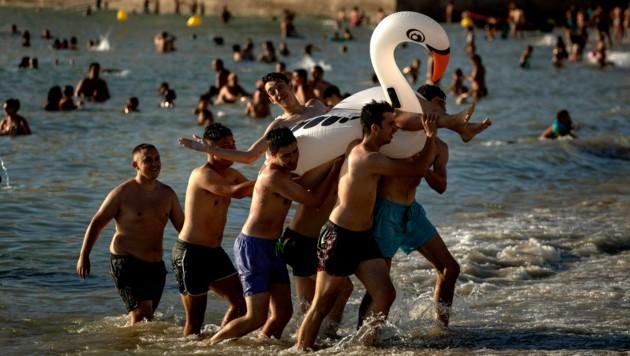Touristen am Strand von Cadiz im Süden Spaniens. Aufgrund schlechter Nachrichten aus London könnte der Badespaß für englische Urlauber schon bald vorbei sein. (Bild: AP)