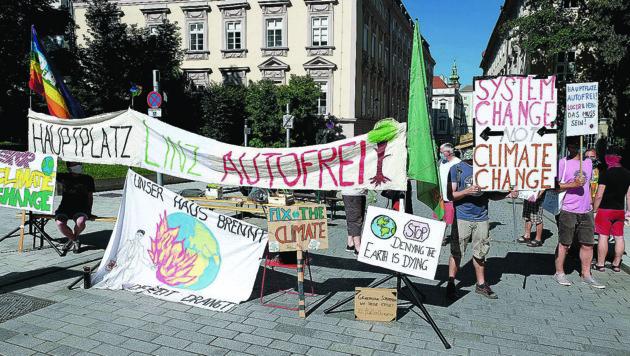 """Die Aktivisten von """"AUTOFREItag fürs Klima"""" sperren den Linzer Hauptplatz für die Durchfahrt (Bild: Horst Einöder/ Flashpictures)"""