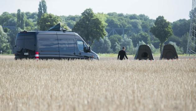 Zelte und ein Fahrzeug der Polizei stehen auf einem Feld in der Nähe einer Kleingartenanlage in der Region Hannover. (Bild: APA/dpa/Julian Stratenschulte)