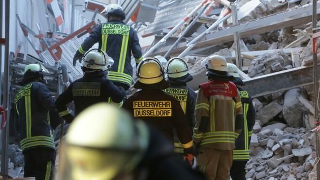 Feuerwehrleute stehen in einer Hauseinfahrt vor Bauschutt. Im Düsseldorfer Zentrum waren bei Bauarbeiten am Montag Teile eines Gebäudes eingestürzt. (Bild: APA/dpa/David Young)