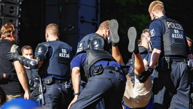 Die Polizei stürmte die Bühne und trug die Redner vom Pult. (Bild: EPA)