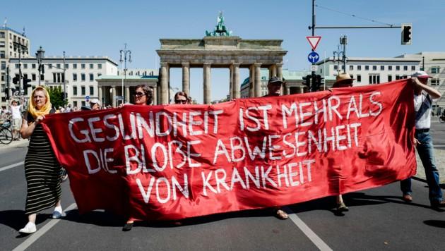 """Mitglieder der Gruppierung """"Querdenken 711"""" spielen auf diesem Transparent bei der aufgelösten Demo in Berlin auf den Spruch """"Frieden ist mehr als die bloße Abwesenheit von Krieg"""" an. (Bild: AFP)"""