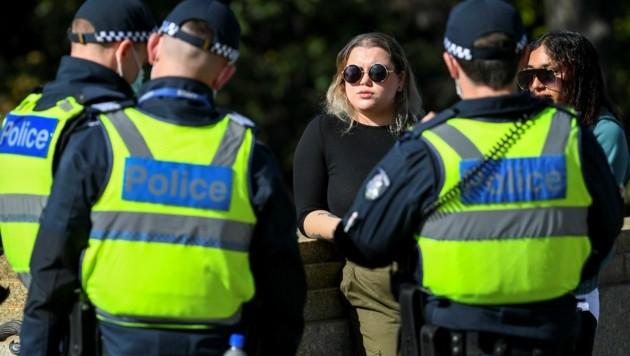 Die Polizei in Melbourne verteilt Strafzettel an zwei Frauen, die - entgegen der Vorschriften - keine Gesichtsmaske in der Öffentlichkeit tragen. (Bild: AFP)
