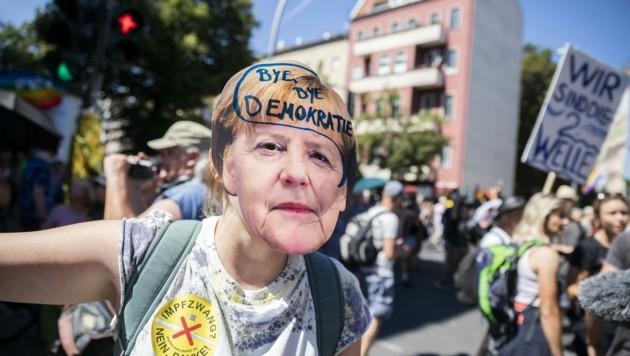 """""""Bye, bye Demokratie"""" steht auf dieser Merkel-Maske bei einer Demo in Berlin unter dem Motto """"Tag der Freiheit""""."""