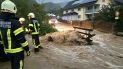 Einsatzkräfte der Feuerwehr Schattleiten bei ihrem Einsatz an einer überfluteten Straße in Oberösterreich. (Bild: APA/BFK STEYR-LAND)