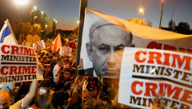 Für diese Demonstranten ist Benjamin Netanyahu kein Premier-, sondern ein Verbrecherminister. (Bild: APA/AFP/MENAHEM KAHANA)