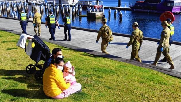 Eine Gruppe von Soldaten und Polizisten inspizieren die Docklands von Melbourne.