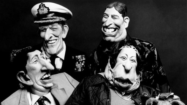 """Prinz Philip, Prinz Andrew (rechts hinten), Prinz Charles, die die Queen und ihre Corgis wurden in der Sendung """"Spitting Image"""" als Puppen dargestellt und satirisch aufs Korn genommen."""