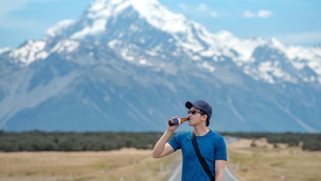 Ein Tourist genießt ein Bier in Neuseeland, im Hintergrund der Mount Cook. (Bild: stock.adobe.com, Krone KREATIV)