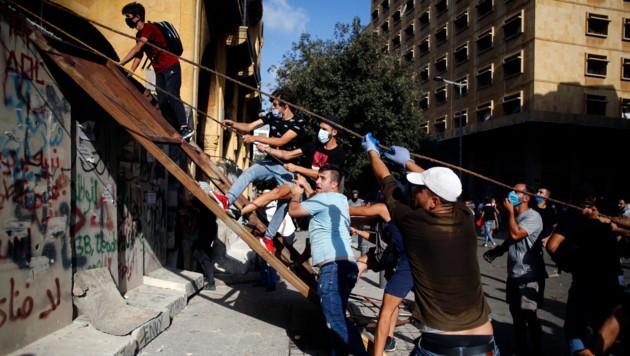 Demonstranten überwinden eine provisorische Schutzmauer, die um das Regierungsviertel errichtet wurde. (Bild: AP)