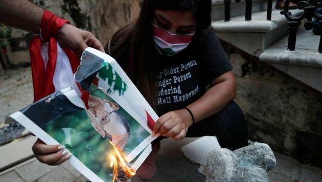 Demonstranten verbrennen ein Bild des libanesischen Präsidenten Michel Aoun. (Bild: AP)
